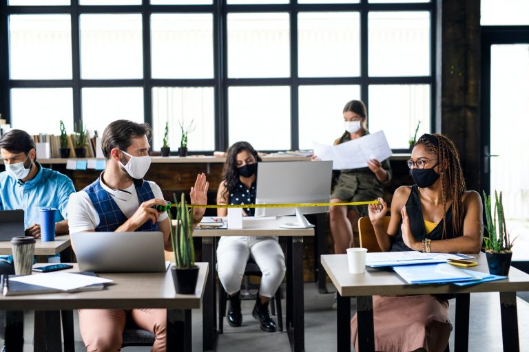 Business people with face masks in office, coronavirus and safe distance concept